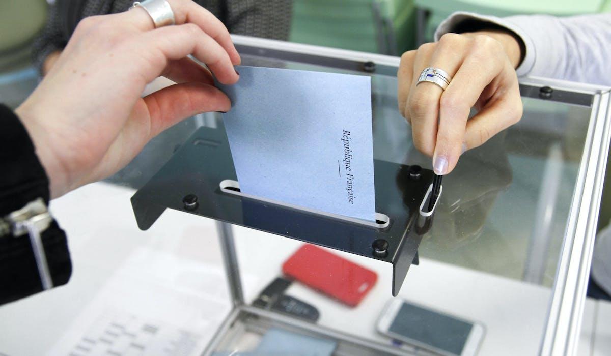 Un homme met son enveloppe dans l'urne lors des élections
