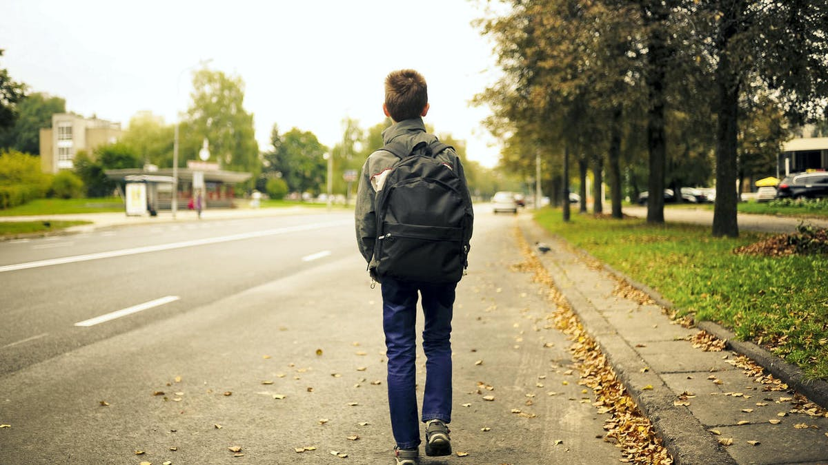 Un enfant tourne le dos à l'école