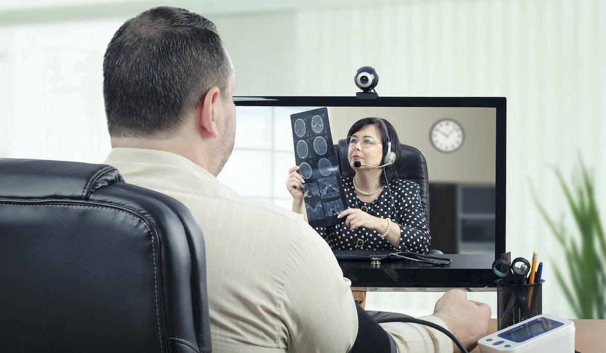 Un patient consulte son médecin par ordinateur