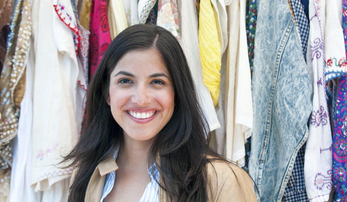 Une jeune femme devant un étal de vêtements