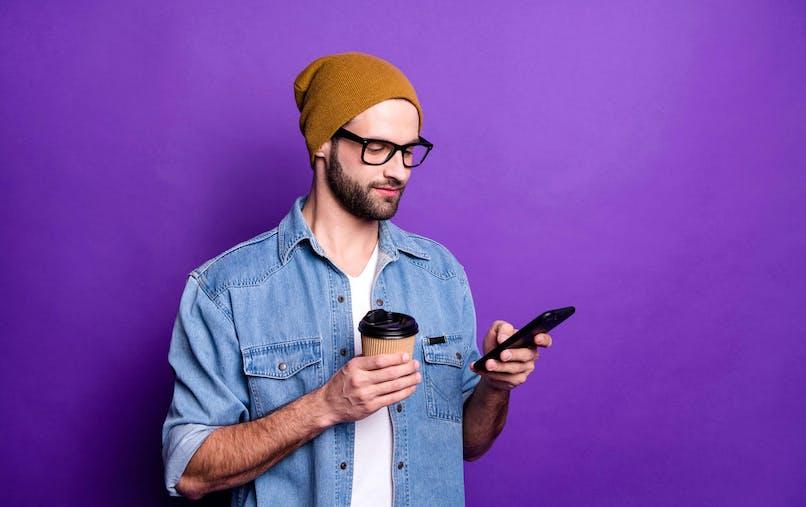Un jeune homme consulte son téléphone portable