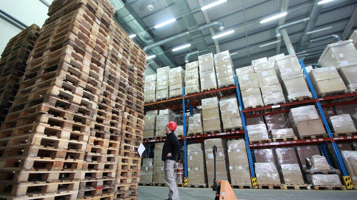 Un entrepôt de stockage et une montagne de palettes, signes d'une activité réduite.