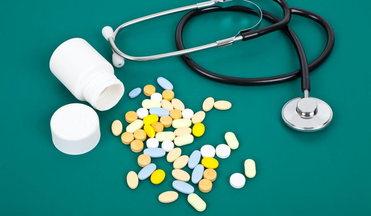 Un stéthoscope, des médicaments posés sur un bureau