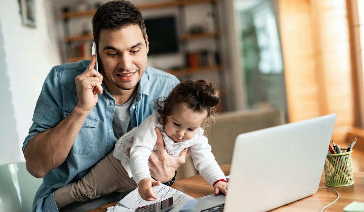 Un homme télétravaille avec son enfant sur les genoux