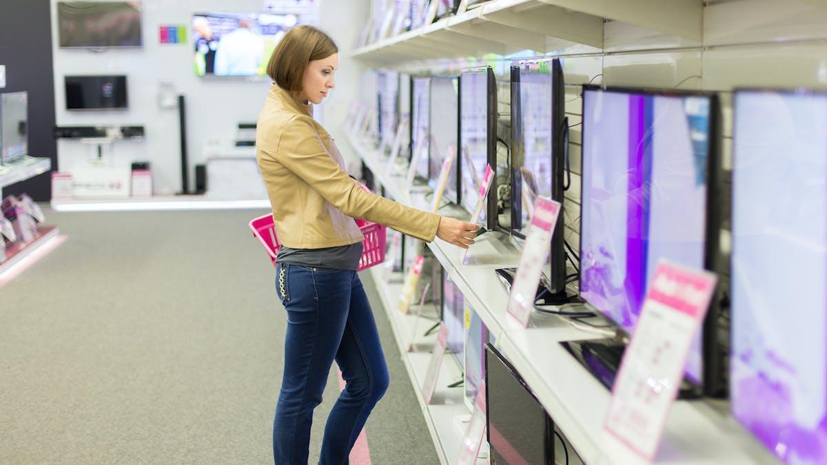 Une cliente regarde les prix des téléviseurs dans un magasin