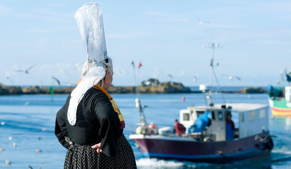 Les marins pêcheurs bretons partent en mer devant une bigoudène