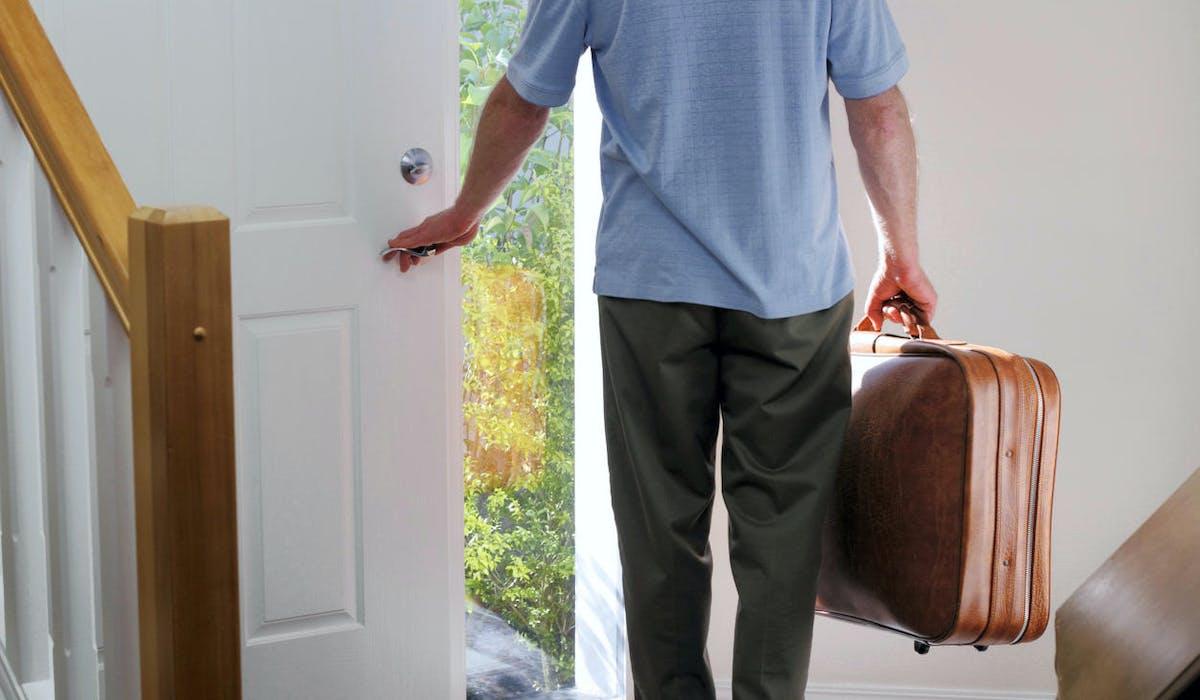 Un homme sort de sa maison une valise à la main