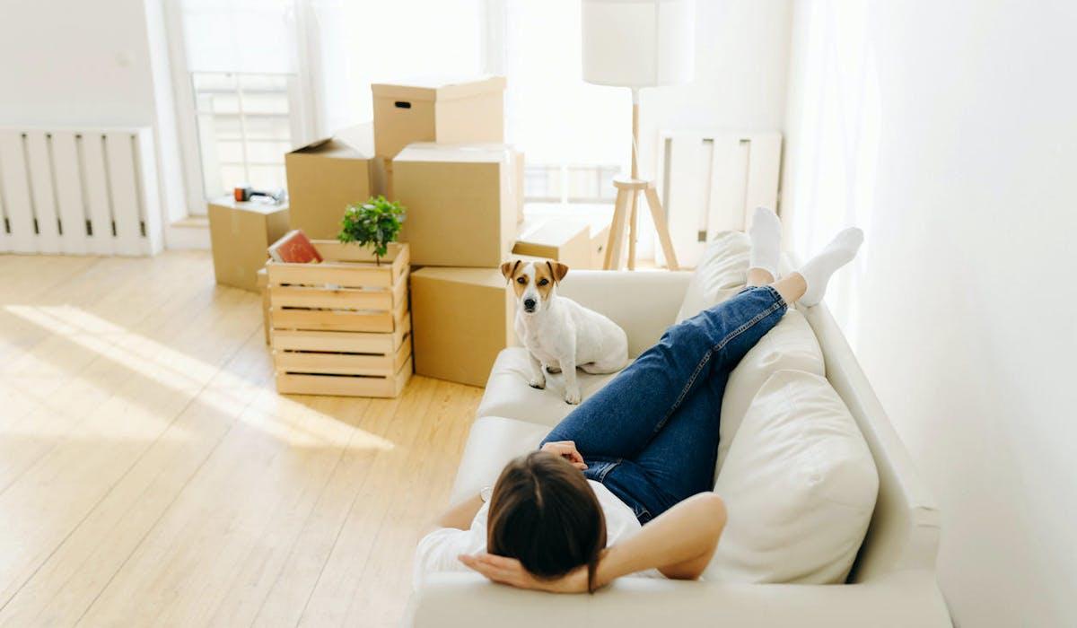 Une femme sur son canapé avec son chien dans son nouvel appartement
