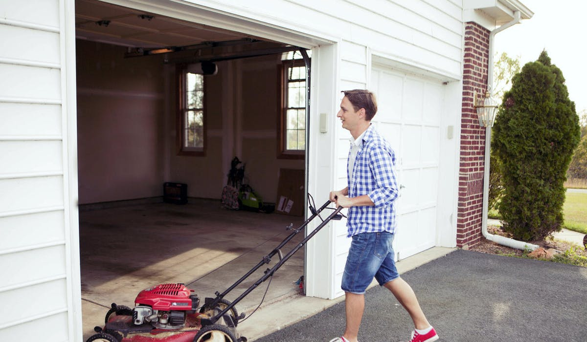 Un homme range une tondeuse à gazon au garage