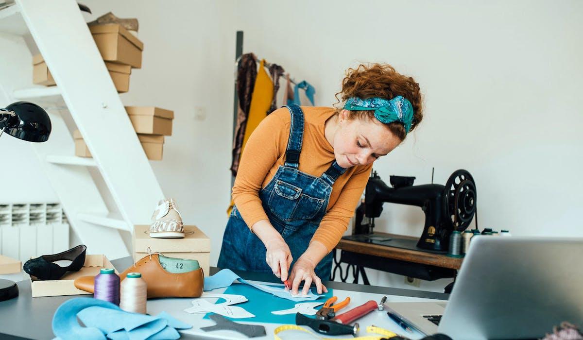 Un jeune femme artisan dans son atelier de création de chaussures