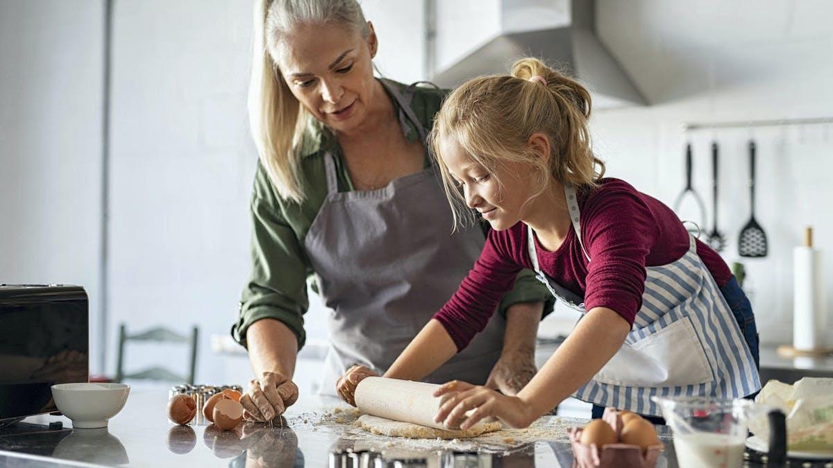 Une petite fille et sa mamie au pair font de la pâtisserie