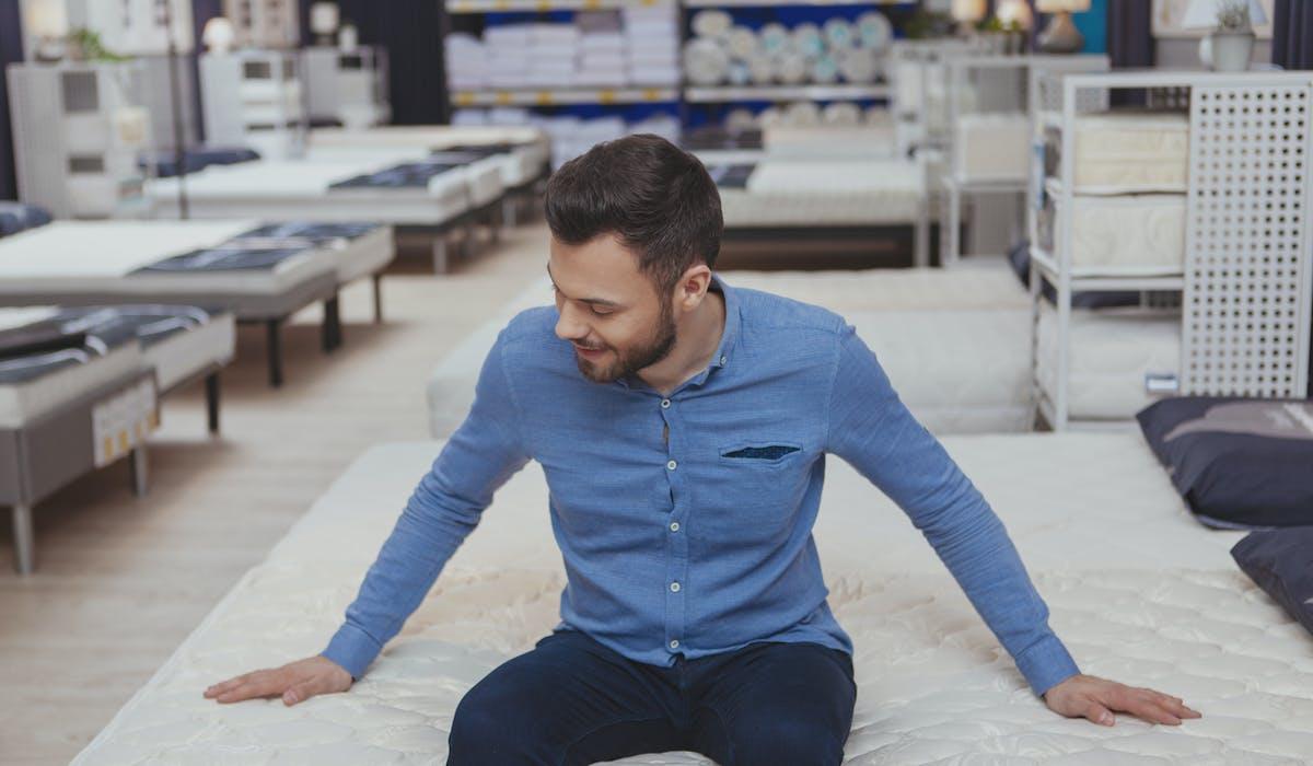 Un client essaie un matelas dans un magasin avant de l'acheter