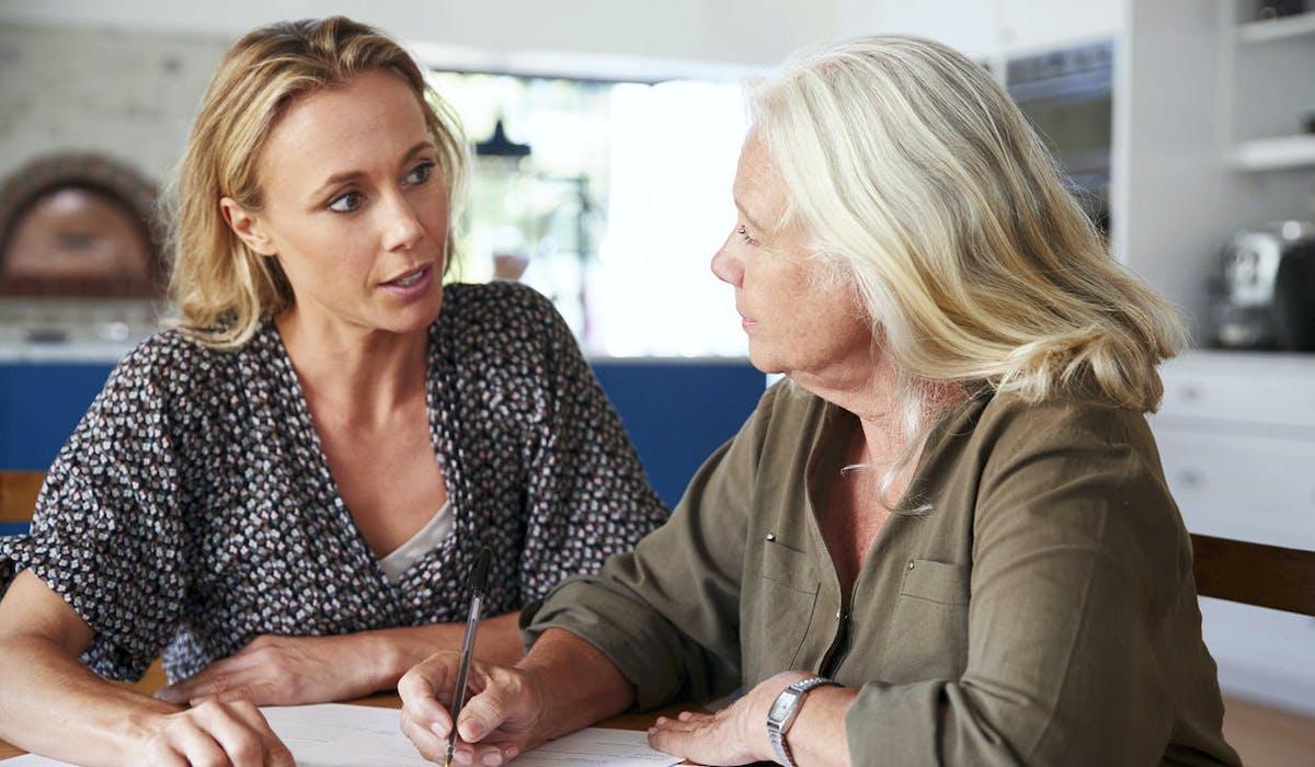 Une fille et sa mère discutent autour de documents administratifs