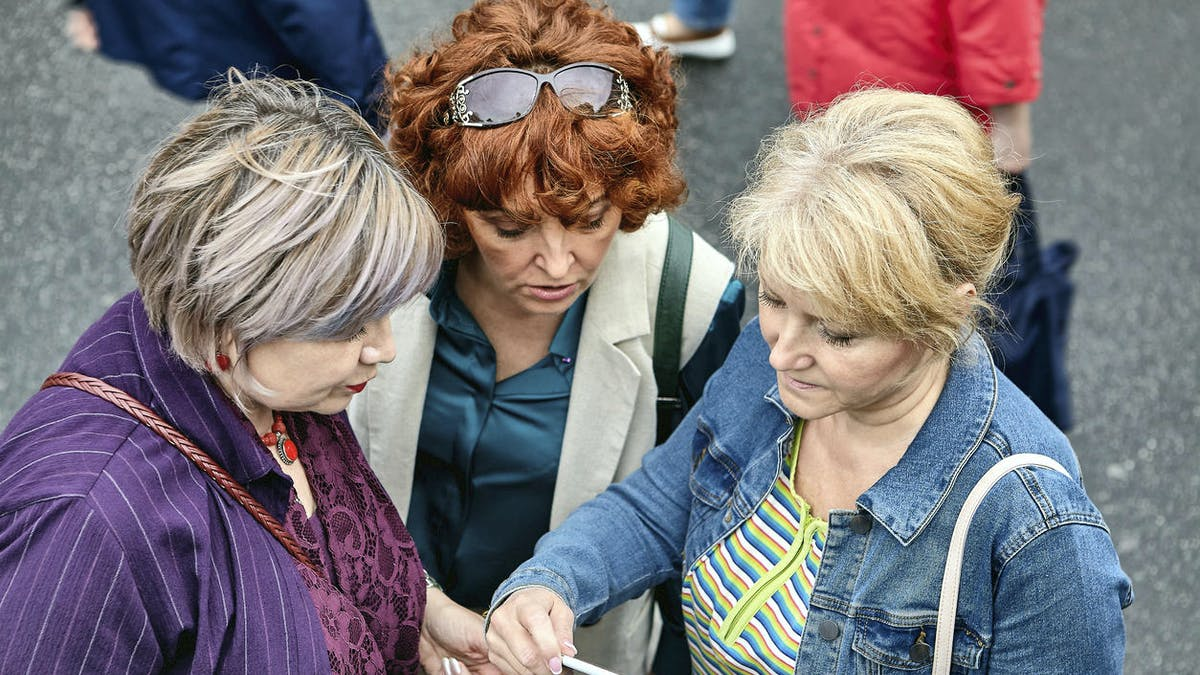 Trois femmes lisent un article sur un téléphone portable