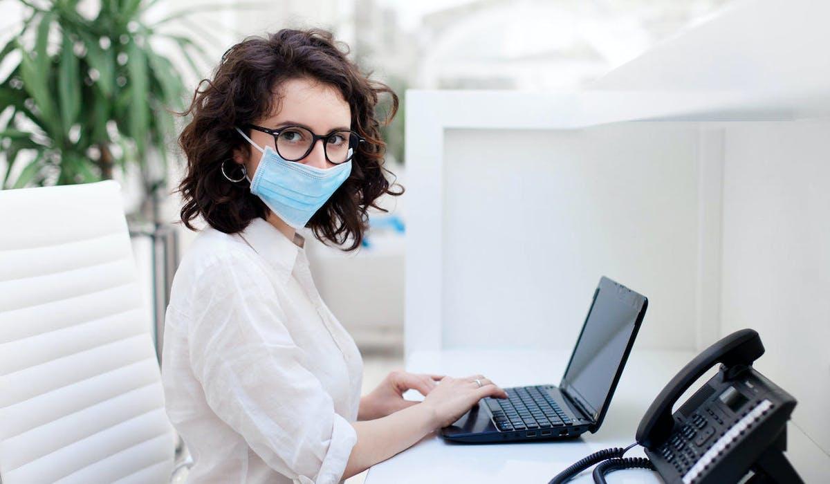 Femme réceptionniste, masque, ordinateur