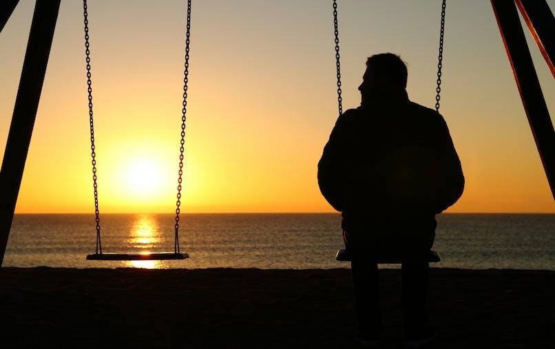 Océan, soleil couchant, balançoires, homme