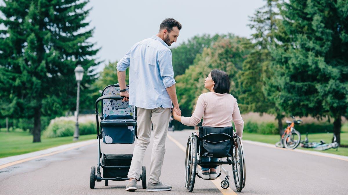 Homme debout, femme en fauteuil roulant, poussette