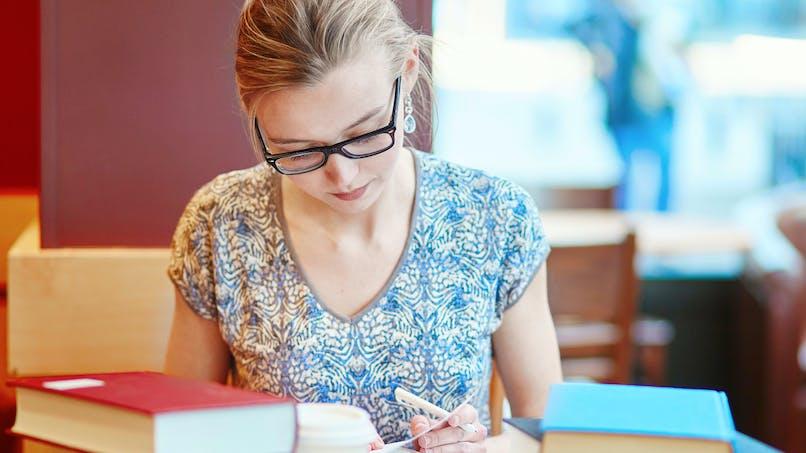 Jeune femme, concentrée, lunettes, livres