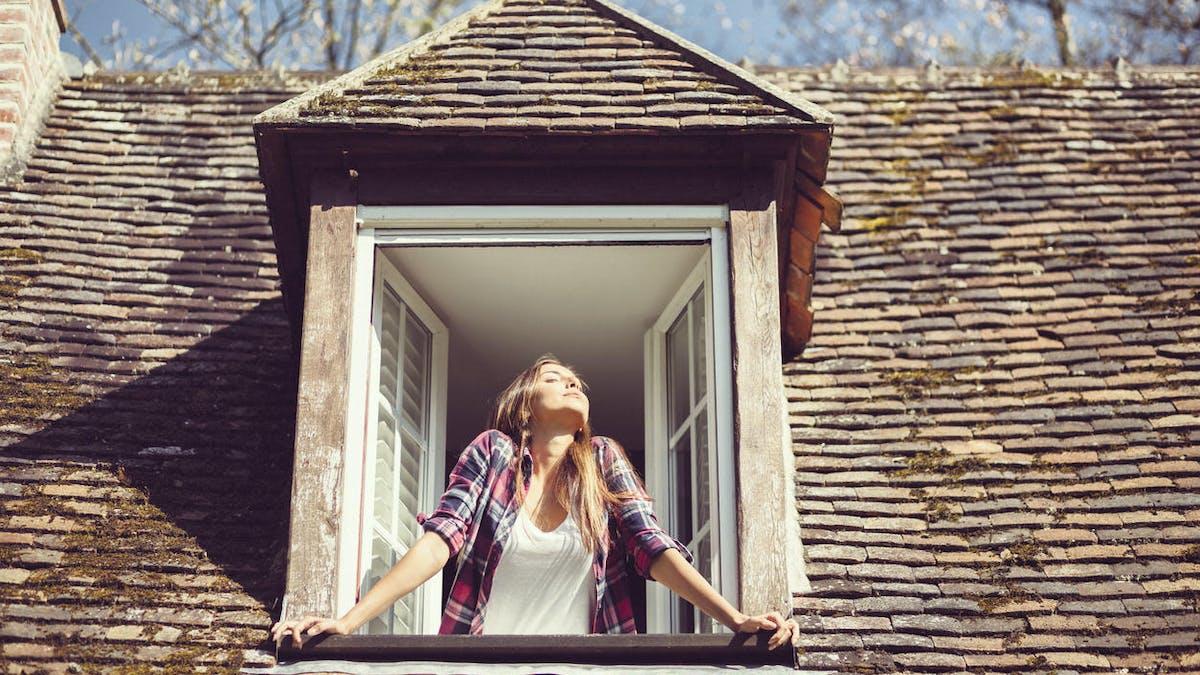 Maison, dernier étage, fenêtre, jeune femme contente