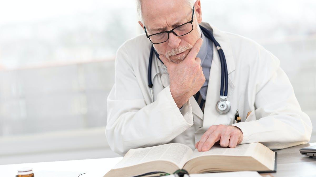 Médecin concentré, blouse, stéthoscope, livre